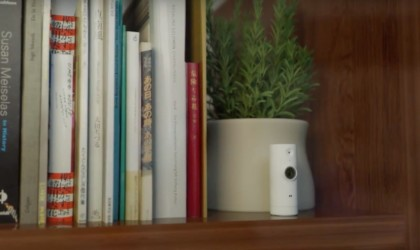 A small white home security cam is on a bookshelf next to a potted plant.