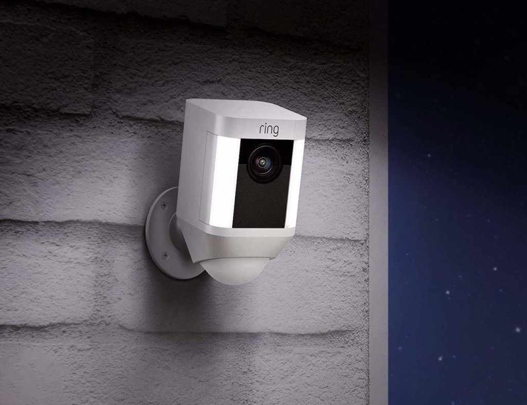 A security camera with lights is mounted on white bricks.