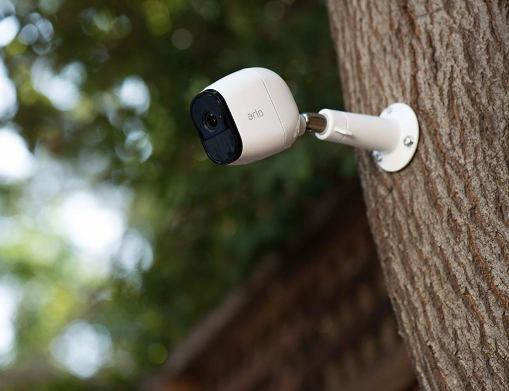 A white home security cam is mounted to a tree.