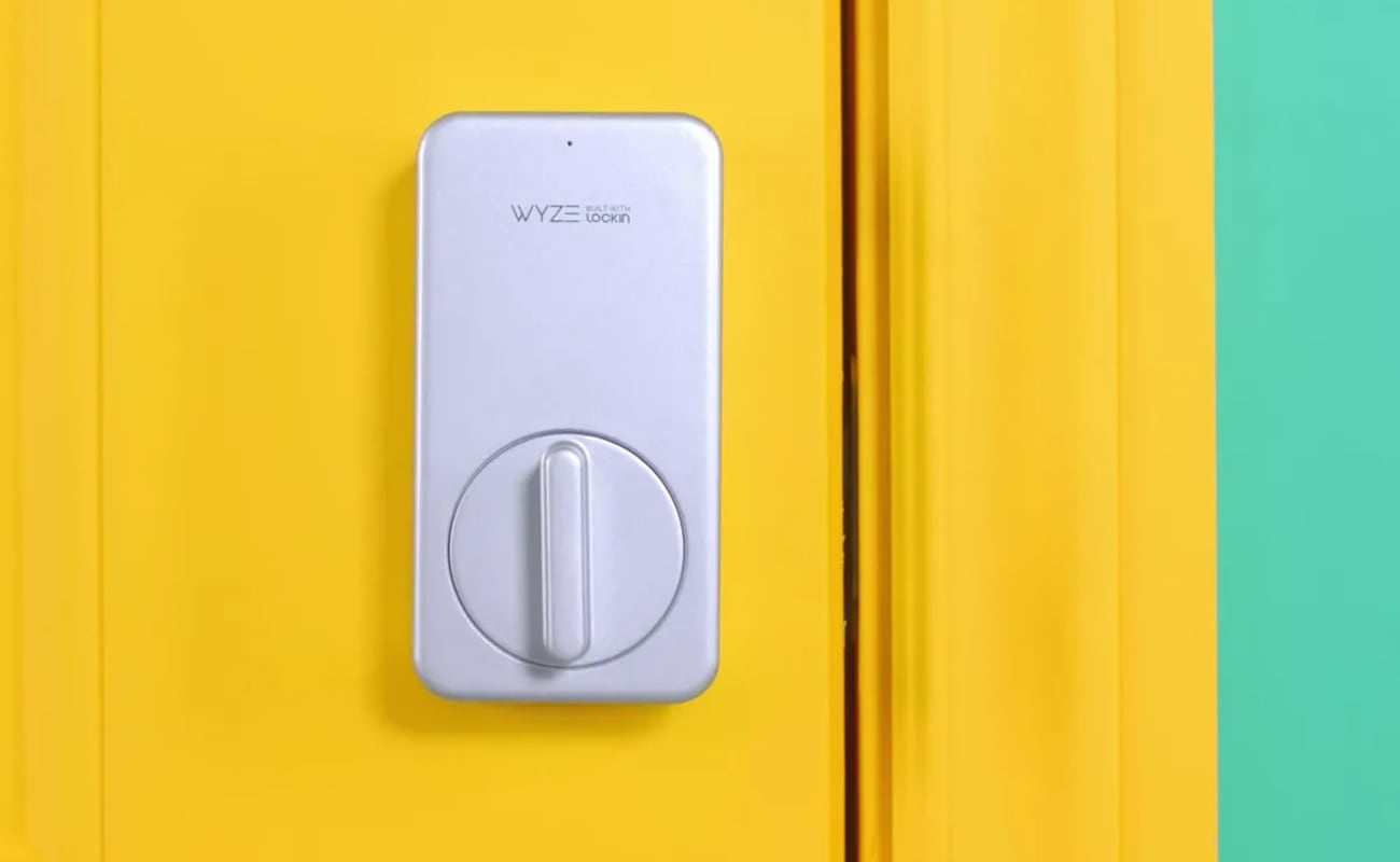 The wireless smart lock is installed on a yellow door.