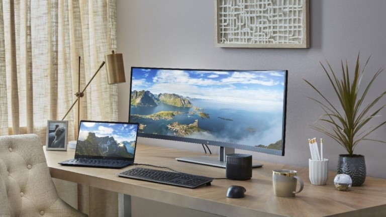 A wide computer monitor on a desk