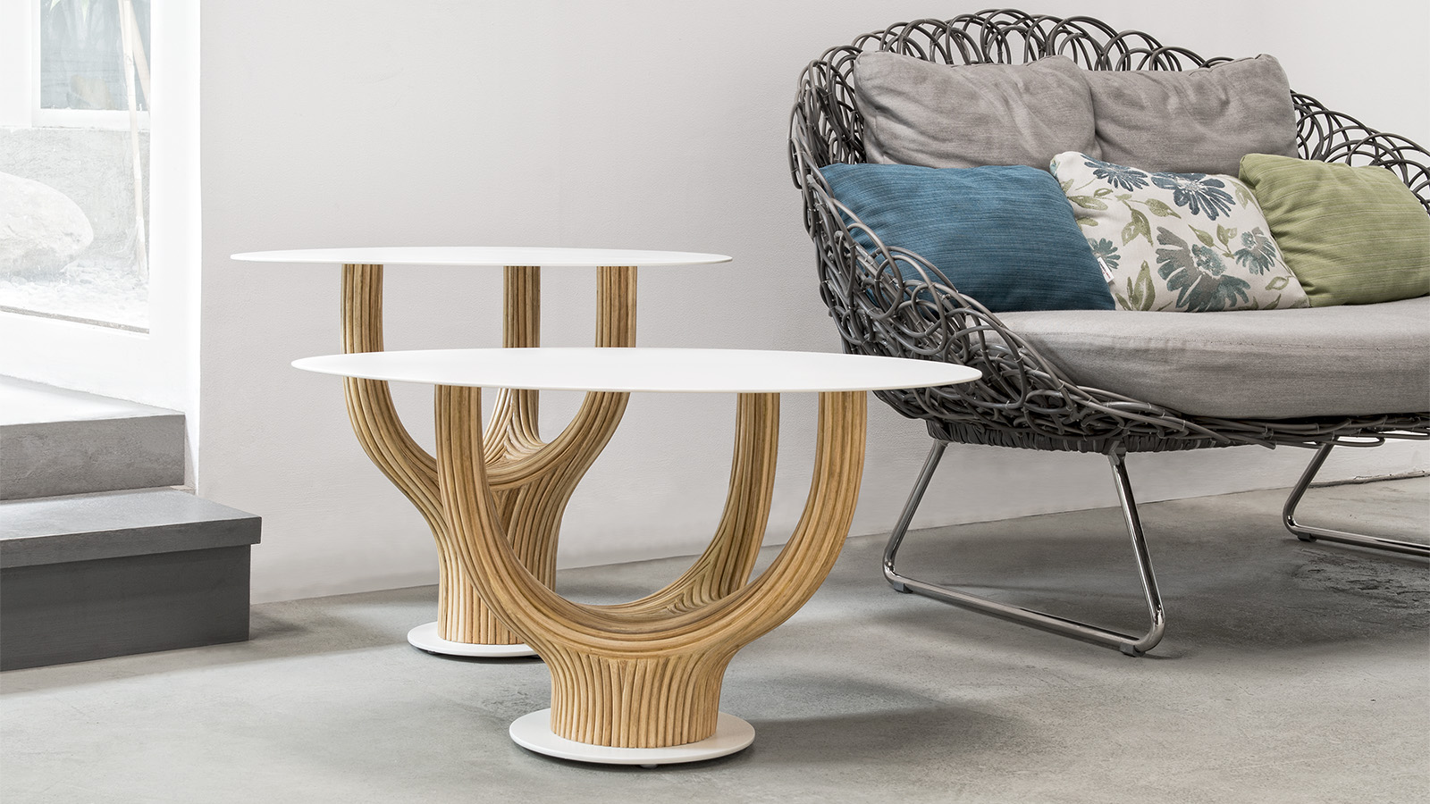 Kenneth Cobonpue Acacia table collection is made of rattan wood with a glass top