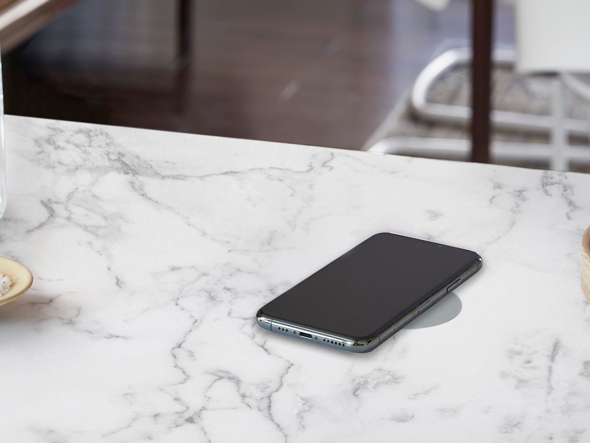 Humanscale NeatCharge 10 W wireless charger subtly attaches to the bottom of a desk